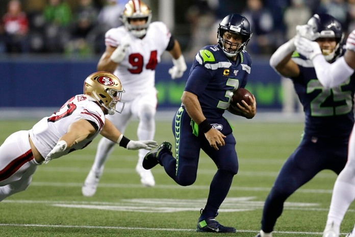 Seattle Seahawks quarterback Russell Wilson (3) is chased by San Francisco 49ers' Nick Bosa on a carry during the second half of an NFL football game, Sunday, Dec. 29, 2019, in Seattle. (AP Photo/Stephen Brashear)