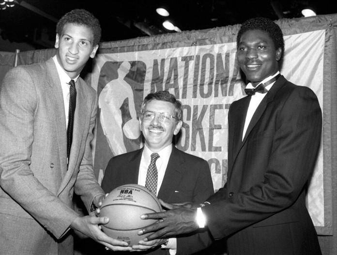 In this June 19, 1984 file photo, NBA commissioner David Stern, center, is flanked by Akeem Olajuwon, right, the No. 1 pick overall by the Houston Rockets, and Sam Bowie, the No. 2 pick overall by the Portland Trail Blazers at the NBA Draft in New York. (AP Photo/Marty Lederhandler, File)