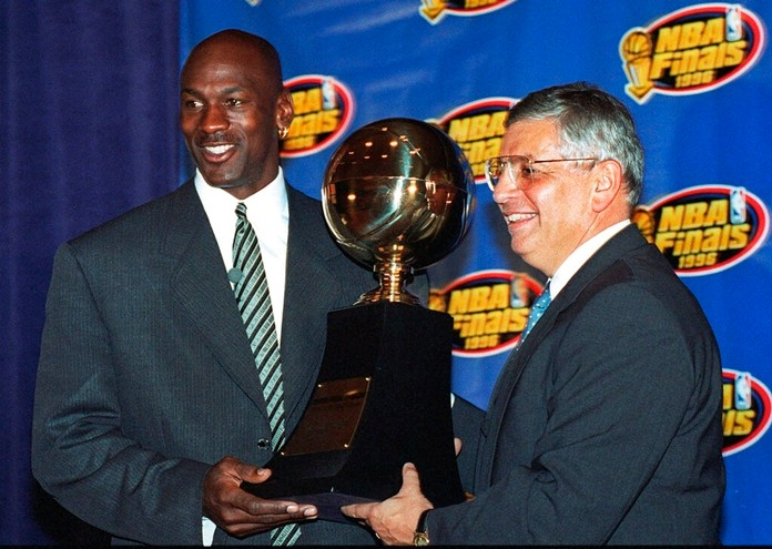 In this June 18, 1996, file photo, Chicago Bulls' Michael Jordan, left, receives the NBA Finals Most Valuable Player trophy from Commissioner David Stern during a ceremony in Chicago. (AP Photo/Charles Bennett, File)