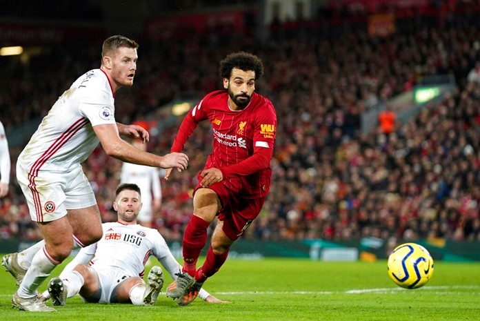 Sheffield United's Jack O'Connell, left, and Liverpool's Mohamed Salah run for the ball during the English Premier League soccer match between Liverpool and Sheffield United at Anfield Stadium, Liverpool, England, Thursday, Jan. 2, 2020. (AP Photo/Jon Super)