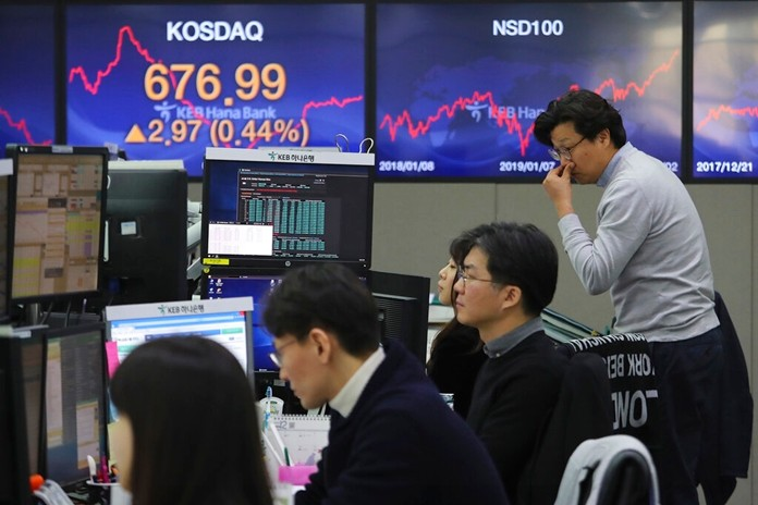 Currency traders watch monitors at the foreign exchange dealing room of the KEB Hana Bank headquarters in Seoul, South Korea, Friday, Jan. 3, 2020. (AP Photo/Ahn Young-joon)