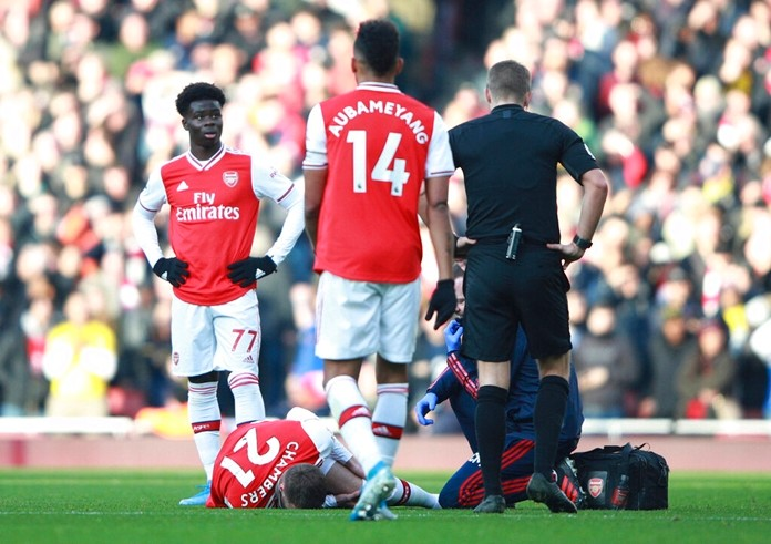 Arsenal's Calum Chambers lies injured on the pitch during the English Premier League soccer match between Arsenal and Chelsea, at the Emirates Stadium in London, Sunday, Dec. 29, 2019. (AP Photo/Ian Walton)