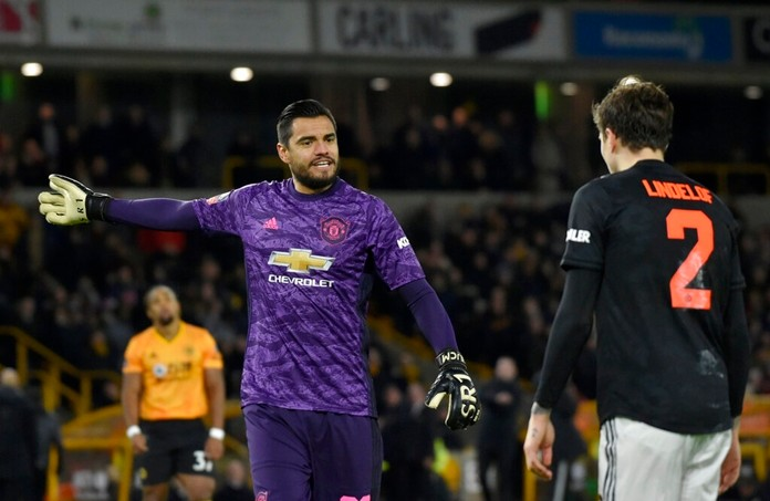 Manchester United's goalkeeper Sergio Romero, left, speaks with Manchester United's Victor Lindelof during the English FA Cup third round soccer match between Wolverhampton Wanderers and Manchester United at the Molineux Stadium in Wolverhampton, England, Saturday, Jan. 4, 2020. (AP Photo/Rui Vieira)