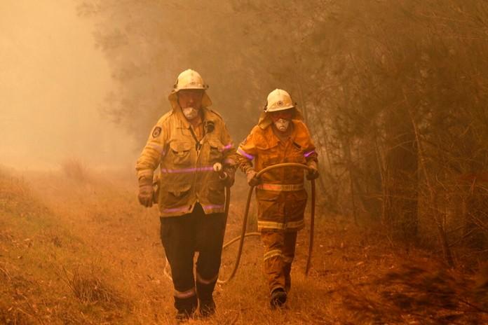 Firefighters drag their water hose after putting out a spot fire near Moruya, Australia, Saturday, Jan. 4, 2020. (AP Photo/Rick Rycroft)