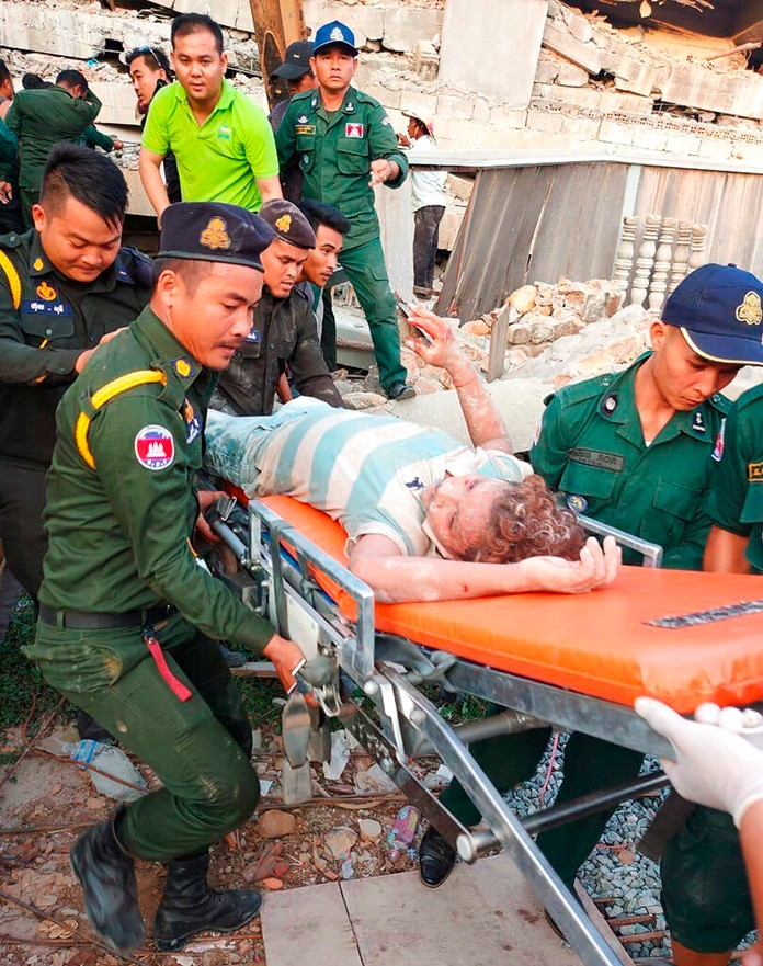 Emergency workers carry a survivor from the debris after a building collapsed in Kep province, Cambodia, Friday, Jan. 3, 2020. At least two construction workers were killed when a seven-floor building collapsed in the southern Cambodian town of Kep on Friday, according to the police. (Kep province Authority Police via AP)