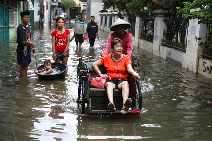 A woman rides a tricycle on a flooded street in Jakarta, Indonesia, Saturday, Jan. 4, 2020. (AP Photo/DitaAlangkara)