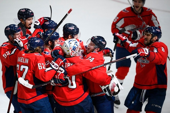 Washington Capitals defenseman John Carlson (74), goaltender Braden Holtby (70), left wing Carl Hagelin (62), left wing Alex Ovechkin (8), of Russia, and others celebrate after an NHL hockey game against the San Jose Sharks, Sunday, Jan. 5, 2020, in Washington. (AP Photo/Nick Wass)