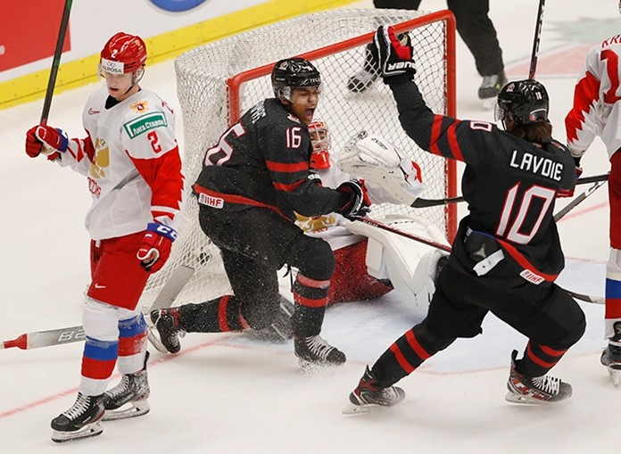 Canada's Akil Thomas, 2nd left, celebrates with Canada's Raphael Lavoie, right, after scoring his sides winning goal past Russia's goaltender Amir Miftakhov, 2nd right, and Russia's Danil Zhuravlyov, left, during the U20 Ice Hockey Worlds gold medal match between Canada and Russia in Ostrava, Czech Republic, Sunday, Jan. 5, 2020. (AP Photo/Petr David Josek)