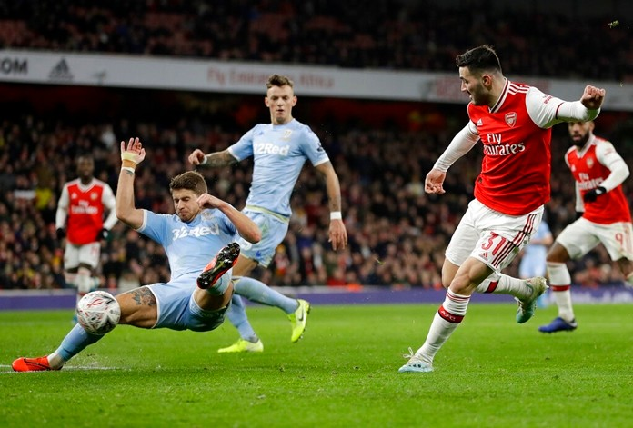 Arsenal's Sead Kolasinac, right, shoots on goal during the English FA Cup soccer match between Arsenal and Leeds United at the Emirates Stadium in London, Monday, Jan. 6, 2020. (AP Photo/Kirsty Wigglesworth)