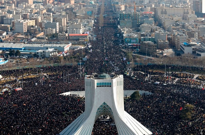Mourners attend a funeral ceremony for Iranian Gen. Qassem Soleimani and his comrades, who were killed in Iraq in a U.S. drone attack on Friday, Jan. 3 as Azadi (freedom) tower is seen in the foreground, in Tehran, Iran, Monday, Jan. 6, 2020. (Office of the Iranian Supreme Leader via AP)