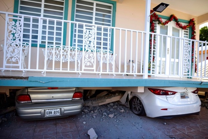 Cars are crushed under a home that collapsed after an earthquake hit Guanica, Puerto Rico, Monday, Jan. 6, 2020.(AP Photo/Carlos Giusti)