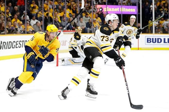 Boston Bruins defenseman Charlie McAvoy (73) moves the puck ahead of Nashville Predators center Matt Duchene (95) in the second period of an NHL hockey game Tuesday, Jan. 7, 2020, in Nashville, Tenn. (AP Photo/Mark Humphrey)