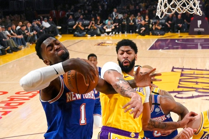 New York Knicks forward Bobby Portis, left, and Los Angeles Lakers forward Anthony Davis reach for a rebound during the first half of an NBA basketball game Tuesday, Jan. 7, 2020, in Los Angeles. (AP Photo/Mark J. Terrill)