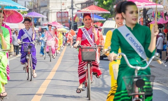 Parade of ladies riding bicycles and holding umbrellas.
