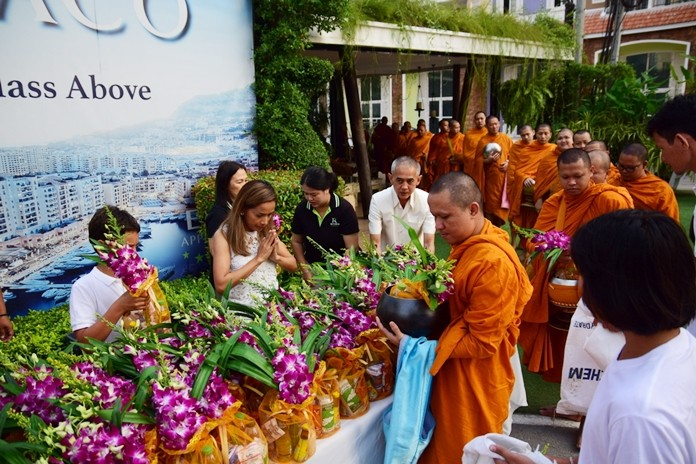 Sukanya Gale together with Sretapol Boonsawad give alms to the Buddhist monks.
