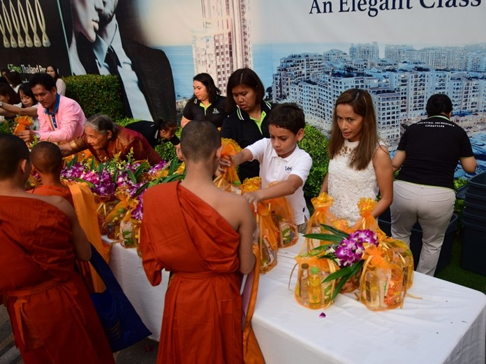 Austin Gale watched over by his mother Sukanya gives alms to the monks.