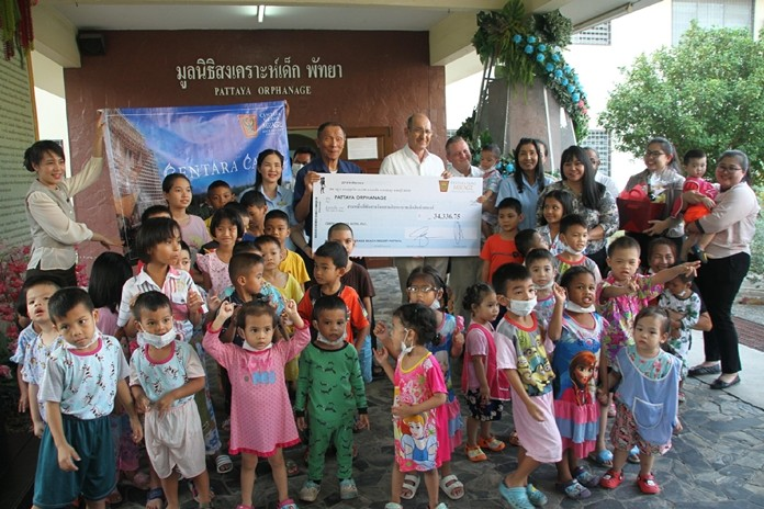 Centara Grand Mirage Beach Resort Area General Manager Denis Thouvard, Asst. GM Yaree Nealsen and resort staff hand over funds raised at the annual Christmas Tree Lighting in December.