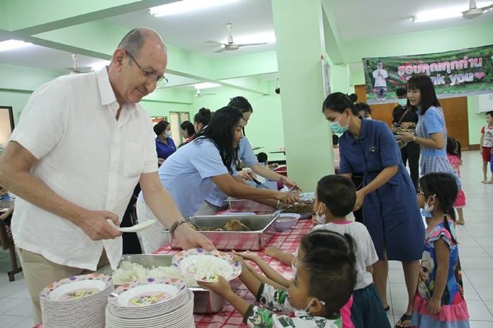 Denis Thouvard helps serve lunch to grateful children.