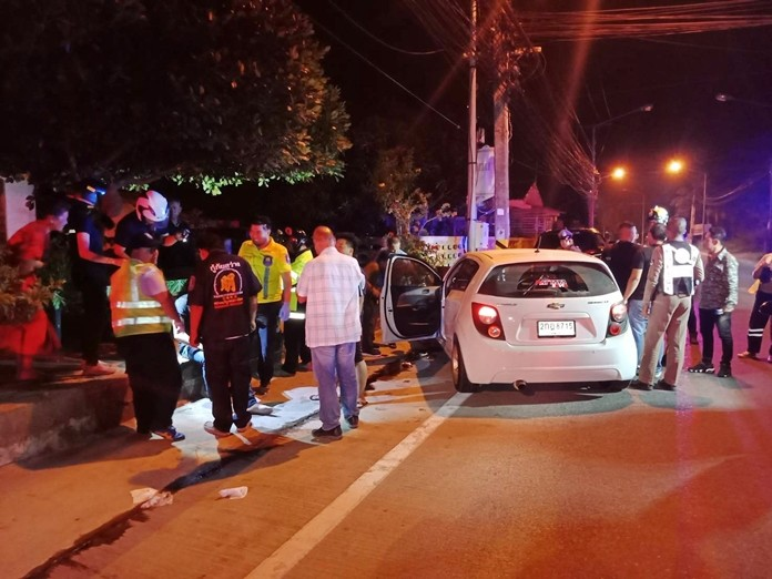 Rescue workers attend to Waranyu Kaewmala who was grazed in the head by a 9mm round and crashed his Chevrolet Sonic into a utility pole.