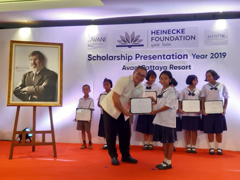 Terapan Chuaprasert Executive Assistant Manager distributes the scholarships while an image of founder William H. Heinecke looks on over his shoulder.