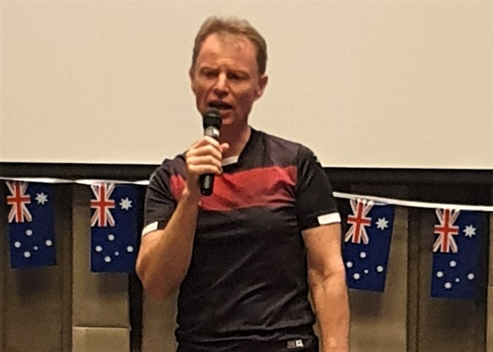 MC Ren Lexander, with several Australian flags behind him, reminds his PCEC audience that it is Australia Day.