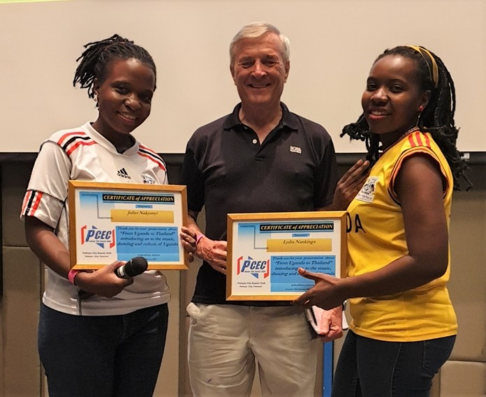 MC Ron Hunter presents PCEC Certificates of Appreciation to Juliett Nakyonyi (in white) and Lydia Nankinga (in yellow) for their interesting and informative presentation on their native Uganda.