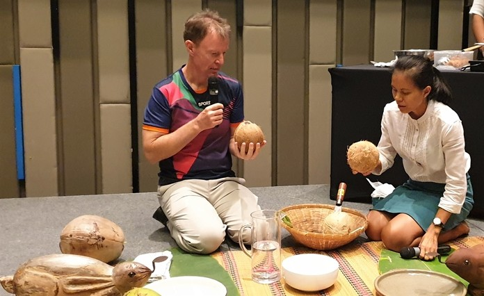 Sasi describes the types of coconuts and their uses in Thai cooking and explains to PCEC Member Ren Lexander, as he contemplates the one in his hand, about how easy it is cut it open.