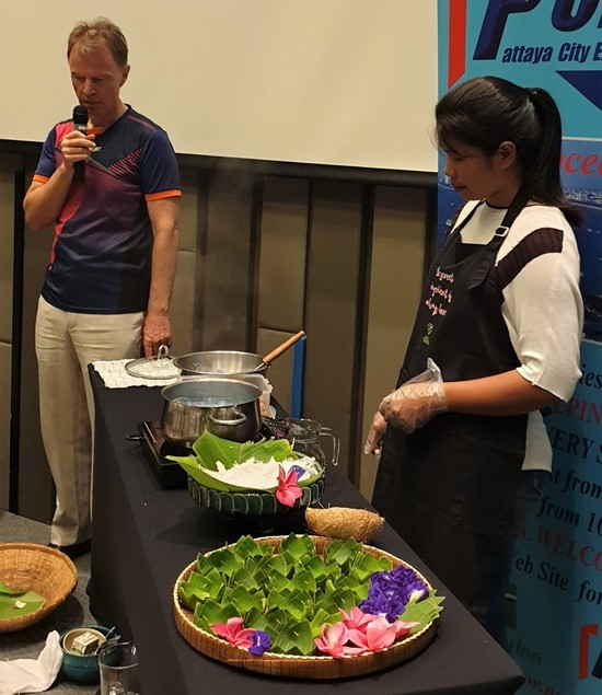 "PCEC member Ren Lexander provides some comments as Sasi's assistant demonstrates the preparation of ""kanom dom,"" a delicious Thai coconut desert. When prepared, samples were provided to the audience."