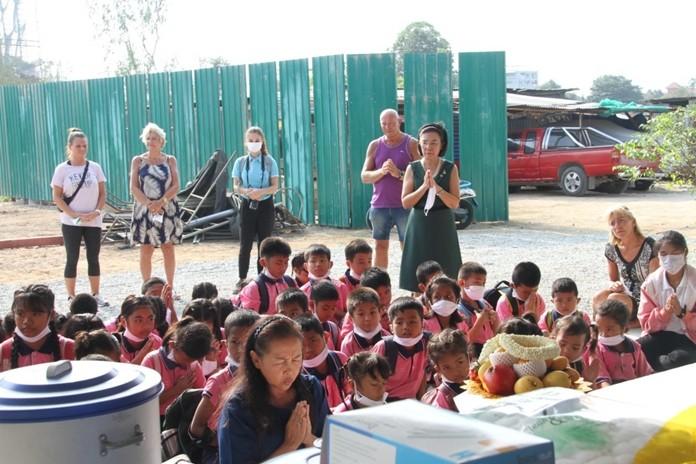 Khun Kru Pim, Principle of ASEAN Education Center leads, HHNFT executives and children in prayer.