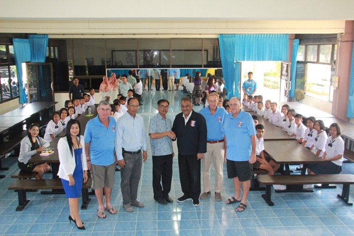 Peter Malhotra shakes hands with school director Apiwat Jaiyungyuen as PSC committee members Noi Emmerson, VP Tim Knight, Willem Lasonder and Stan Rees pose for a photo with students sitting at their new dining/all-purpose tables.