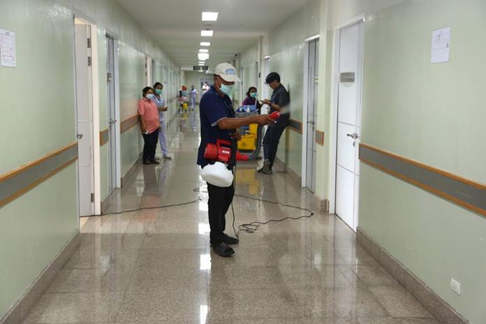 Health office workers spray disinfectant extracted from coconut oil and oxides around Pattaya City Hospital.