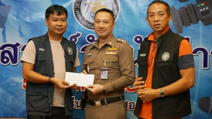 Pol. Col. Pattanachai Pamornpiboon, Banglamung Police Station Superintendent, and Samart Thongrod, President of Pattaya Press Association, present an award to Ton, reporter from BTV.