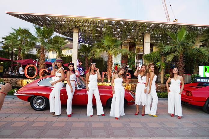Lovely models pose with classic cars outside the open house.