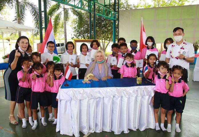 "Dr. Eva Hager, Austrian Ambassador to Thailand, gives children signed copies of the book ""The Grandma in the Apple Tree""."