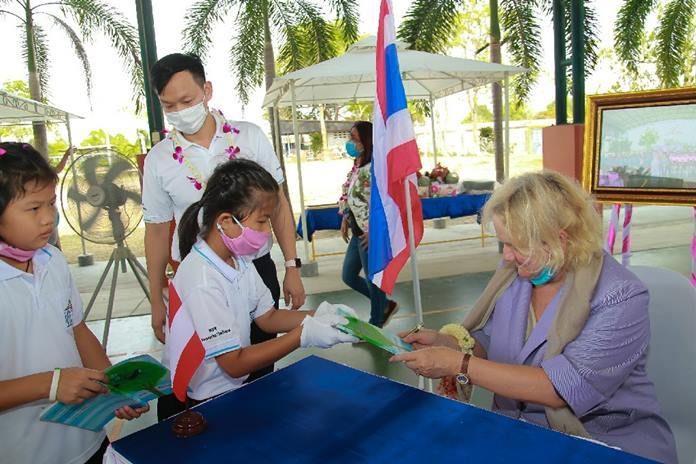 "Dr. Eva Hager, Austrian Ambassador to Thailand, hands out signed copies of the book ""The Grandma in the Apple Tree""."