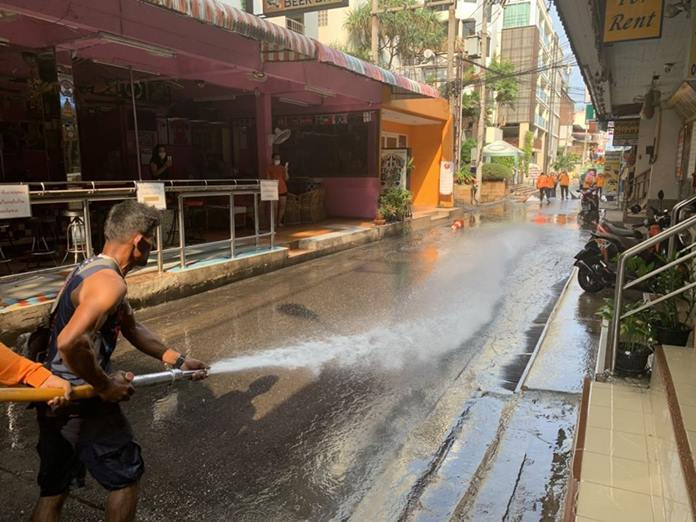 City workers use a high powered water hose down the street of dirt and dust which could harbor any viruses.