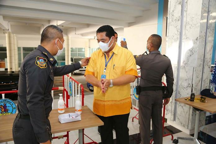 Pattaya Mayor Sonthaya Kunplome gets his temperature checked and lathered with hand gel before being allowed into city hall.