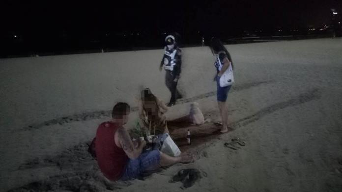 A policeman approaches a group of tourists still enjoying themselves on the beach at night and politely asks them to go home.