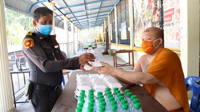 Surachai Yasothorn, abbot of Nalikwanaram Temple – better known as Wat Takhiantia – oversees the distribution of meal boxes and bottled water.