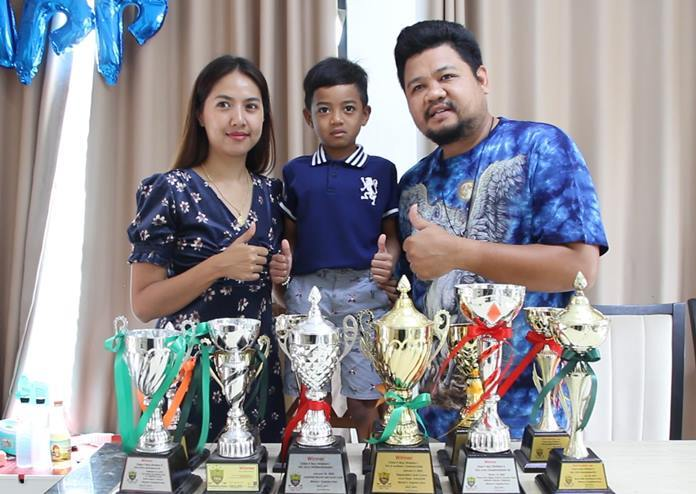 Pro with his proud parents posing with some of his trophies that he'd won at various golf tournaments.