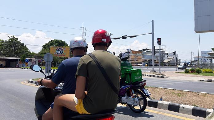 Foreign motorists look on a Grab deliveryman at central Pattaya Sukhumvit HW intersection. The number of home deliverymen in Pattaya increases rapidly amid COVID-19 outbreak