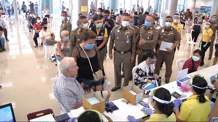 Immigration Bureau officials provide visa extension services to stranded foreigners at the Muang Thong Thani complex temporary center