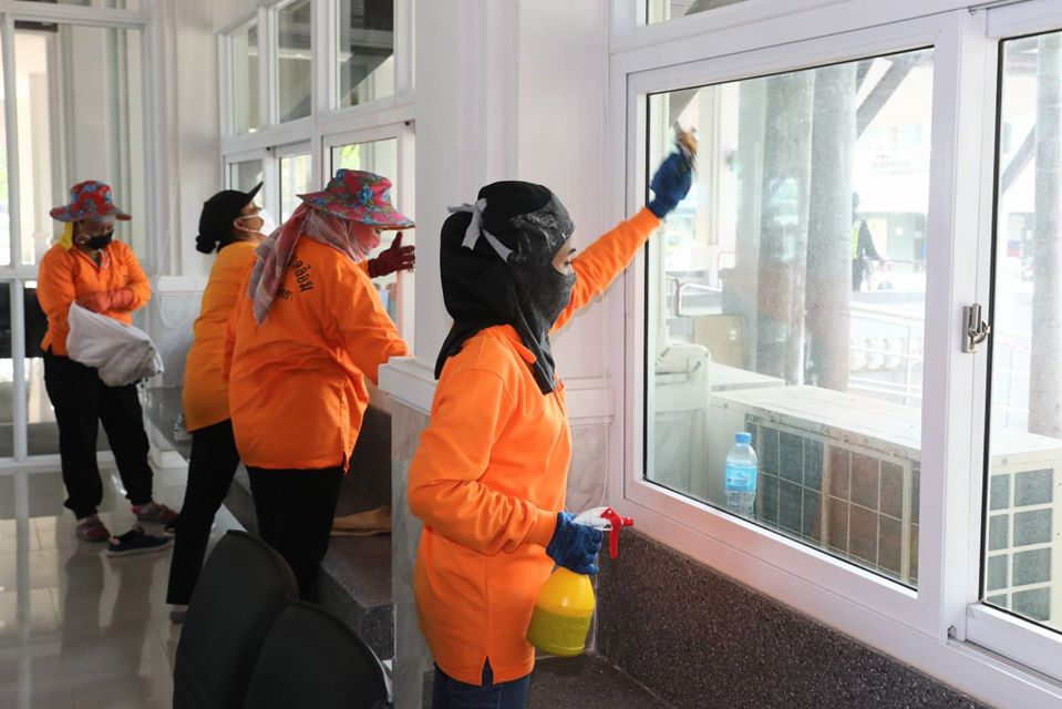 Workers clean the windows in the pier office area with disinfectant.