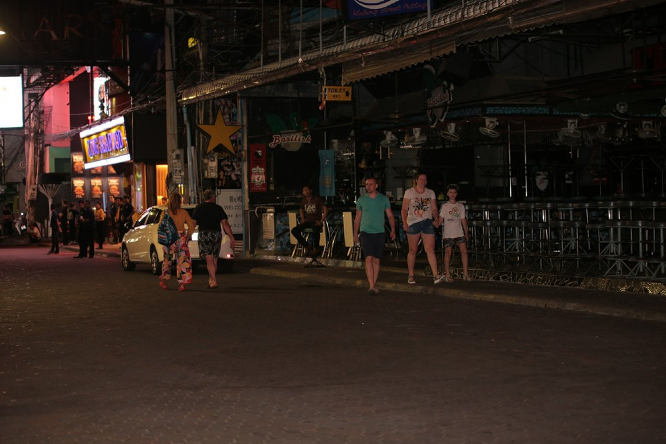 A family walks past a darkened beer bar complex, shut for two weeks.