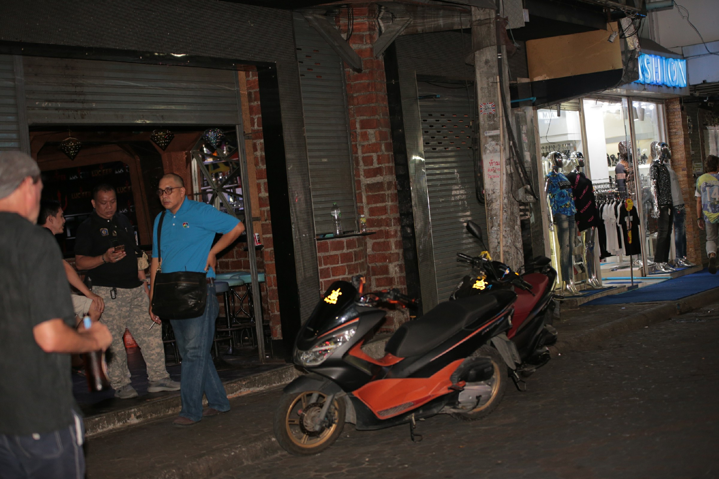 People hang around a closed bar next to a tailor shop open for business on Walking Street.