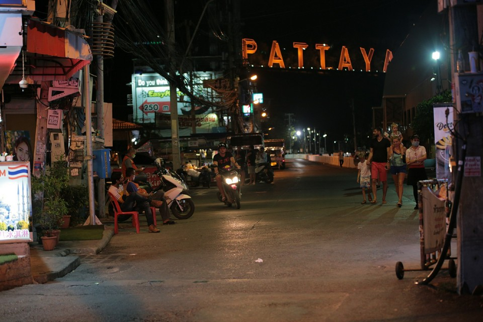 The illuminated Pattaya sign shines bright above Bali Hai Pier as a family takes a stroll and shopkeepers sit idly at the end of the darkened Walking Street.