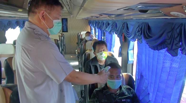 Health officials check temperatures of passengers on an inter province bus.