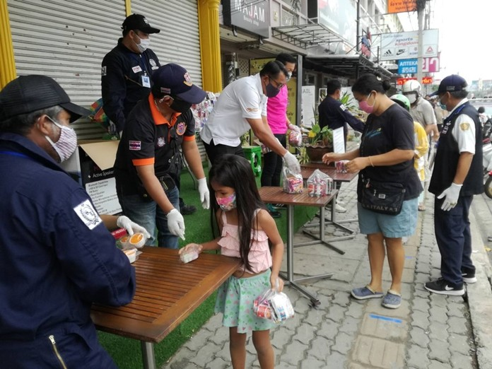 A child picks up a box of food as Passakorn Yoosomboon helps to distribute food to the public.
