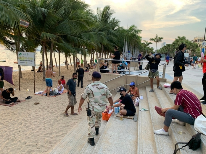 City regulatory-enforcement officers rousted tourists sitting in groups at Jomtien Beach.