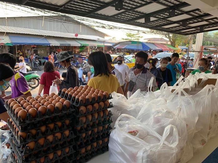 Hundreds of people walk past the distribution tables to pick up food and eggs.
